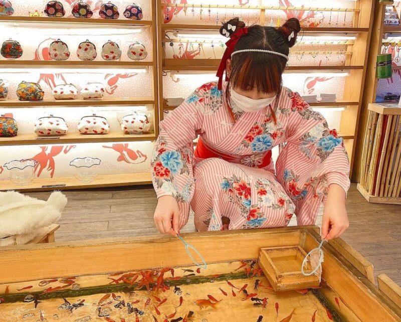 金魚すくいを楽しむ様子(A woman enjoying catching goldfish)